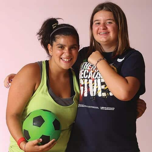 2 girls one with soccer ball