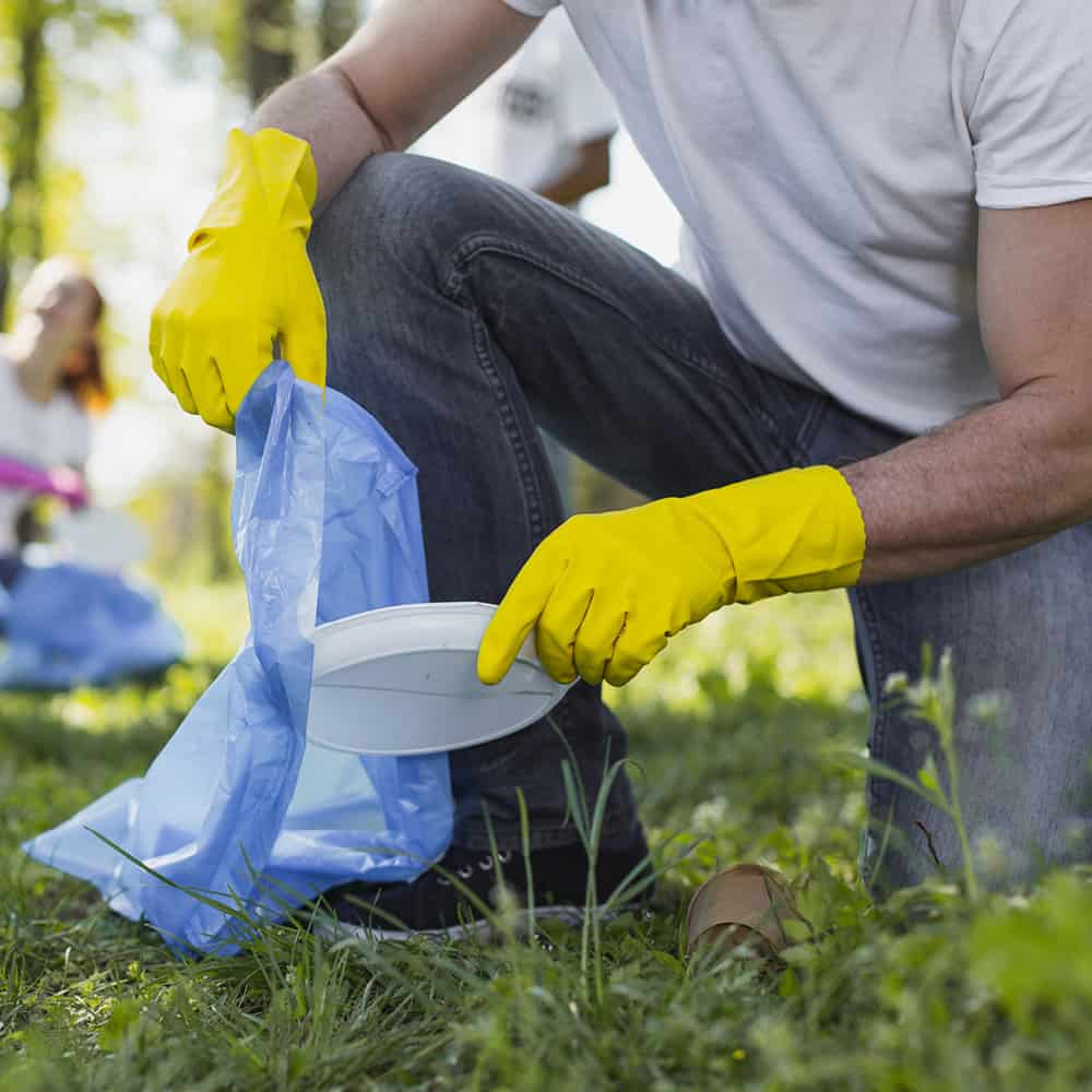 man on one knee with bag and gloves on cleaning up