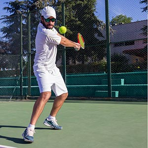 Man with racket hitting tennis ball with back swing