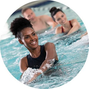 two ladies and a man doing aqua group fitness