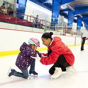 lady bending down assisting little girl on the ice