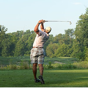 man completing a golf swing on the golf course